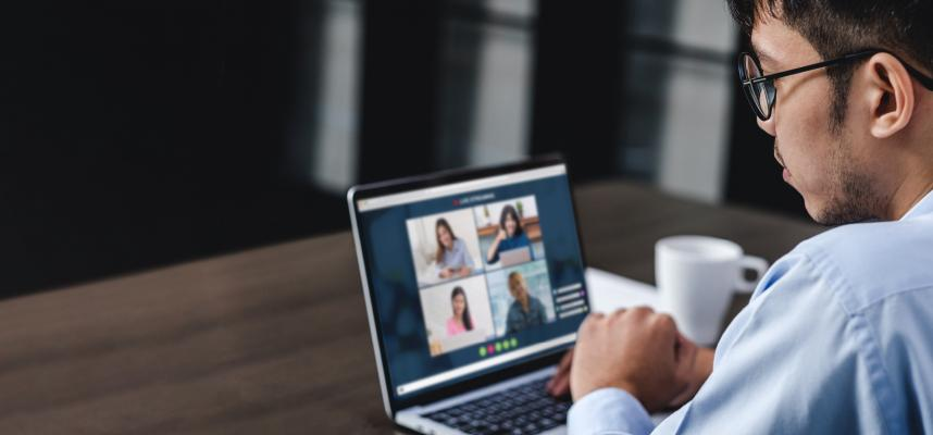 web banner showing man sitting at computer participating in virtual meeting