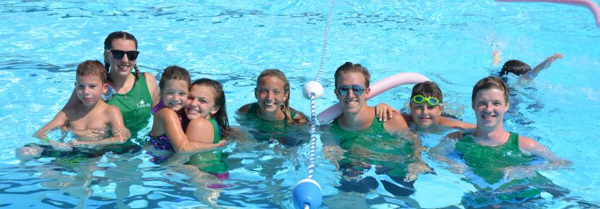 Summer camp leaders in the pool with swimmers